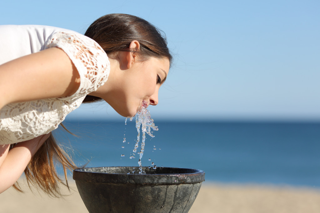 Thirsty woman drinking water from a fountain on the beach in a sunny day